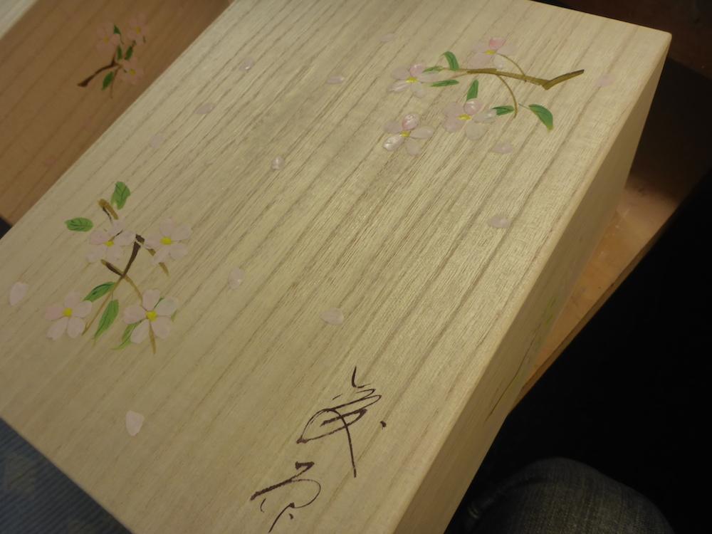桐箱に桜の花びらを手描きをしているところです。