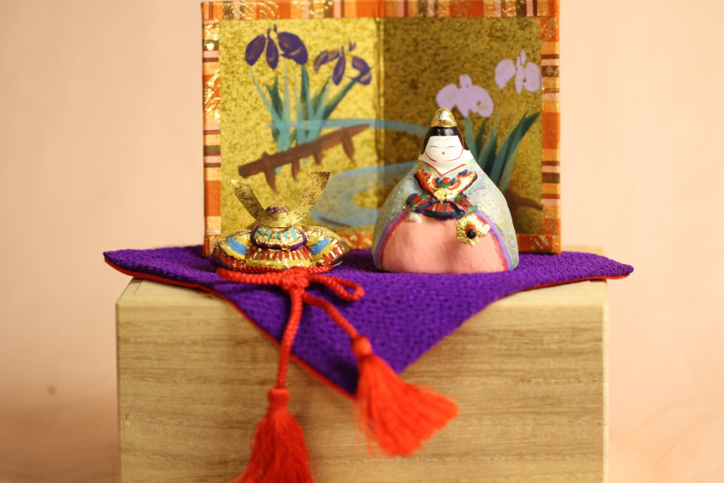 専用のの桐箱の上に紫の布を敷き、童と兜を並べています。