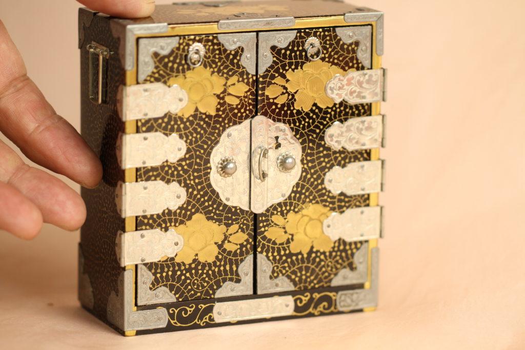 美しい色調の蒔絵箪笥です。大きさは幅10cm、奥行き5cm、高さが11cmに込められた昭和の意気込みが感じられます。