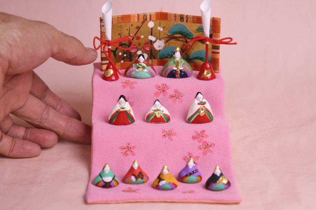 ピンクの布にみかわ工房の小さなお雛様たちをならべています。