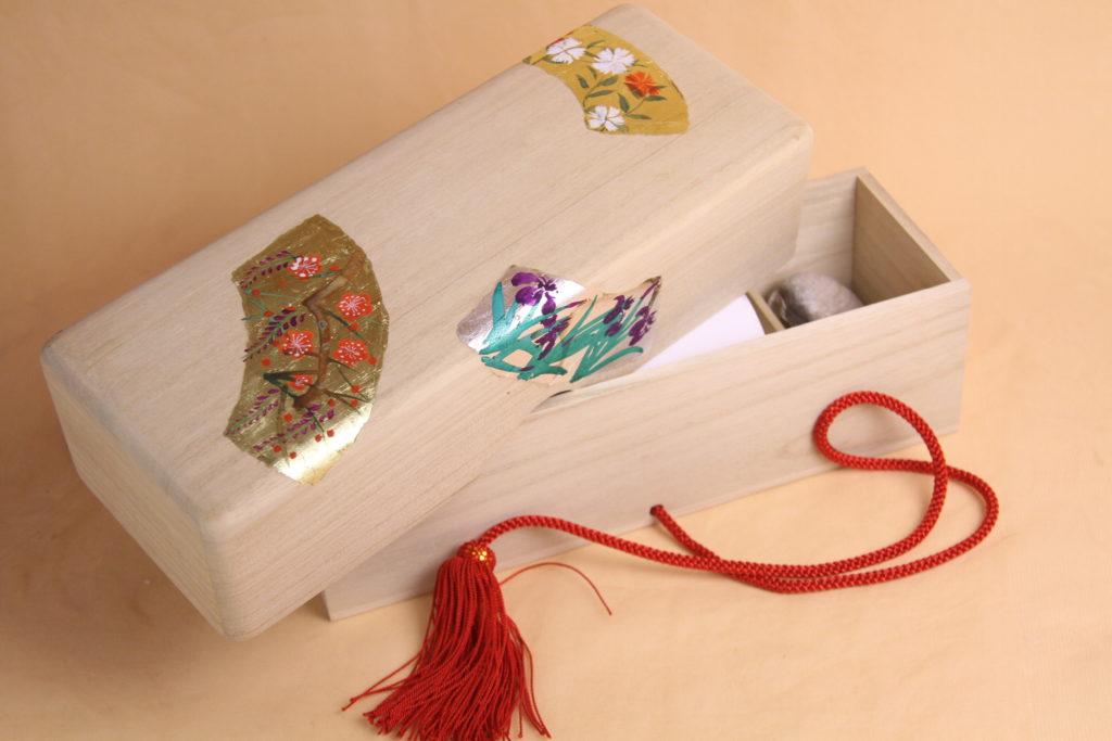 特製の桐箱です。3つの画面には、それぞれ金箔、銀箔を貼り季節の花を手描きしています。