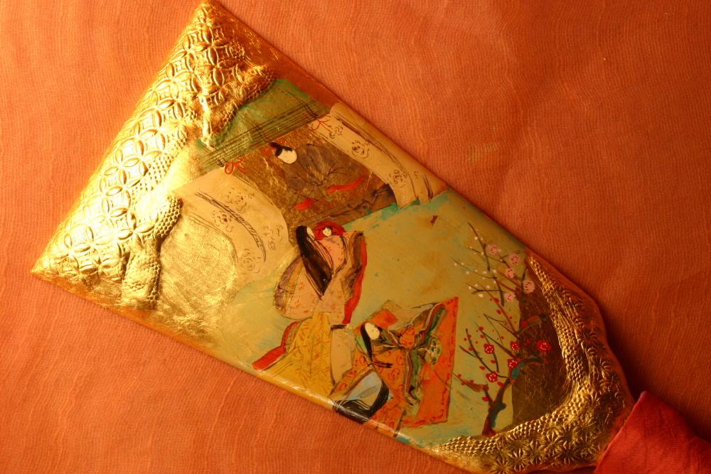 金箔仕上げの羽子板に源氏物語の桐壺のシーンを手書きしています。