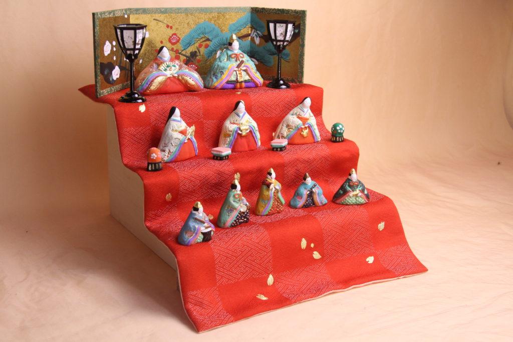 三段飾りの写真で、地模様が入った丹後ちりめんの上に、動きを持たせたお雛様たちが並びます。