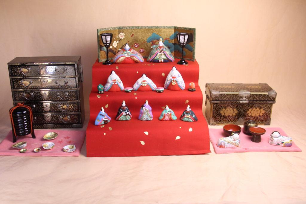 明治の雛道具に帯地の絹地を赤く染めて、コンパクトサイズの三段飾りを作り上げました。