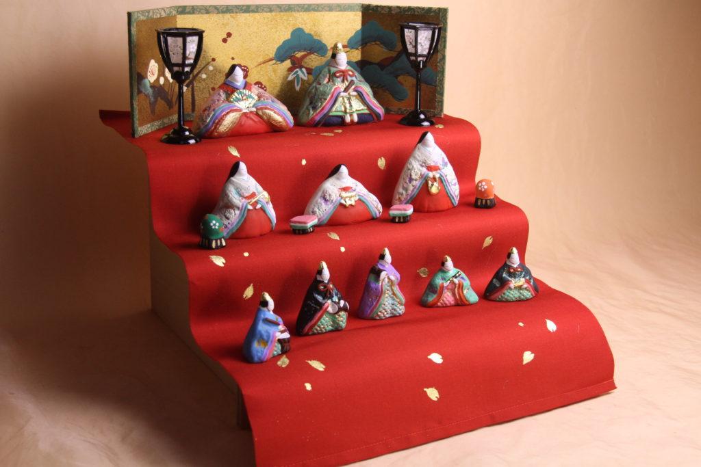 赤い帯地の布をお雛様のひな壇に使っています。